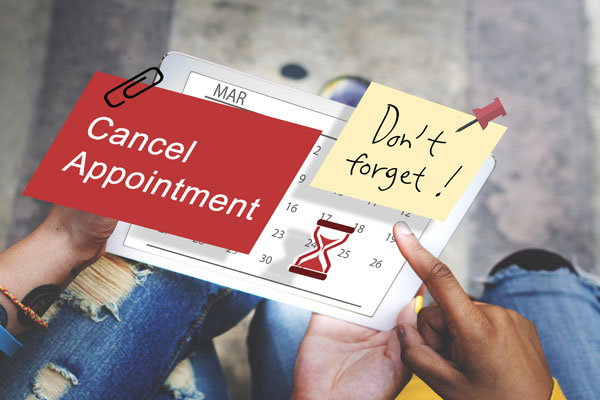 A tablet with a post it that says Don't foget and Cancel Appointment
